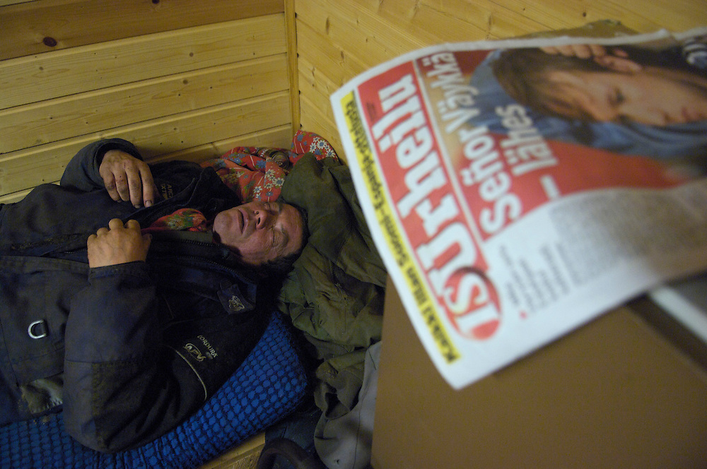 Collapsed from the exhaustion of working three consecutive 14 hour days, Veggai, 58, slumbers in his friends cabin.  Taneli Nakkalajarvi, 28, takes a smoke break from slaughtering reindeer.  He is one of five herders who slaughter, earning only £.40 per reindeer.  Despite the inhospitable Arctic climate reindeer herding has been the livelihood of the Sami for hundreds of years, but amid the economic, technological, and environmental problems of modern society their indigenous culture must increasingly reconcile these radical changes in order to preserve age-old traditions, customs, and mores.