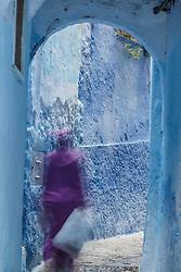Woman walking through blue doorway, Chefchaouen, Morocco