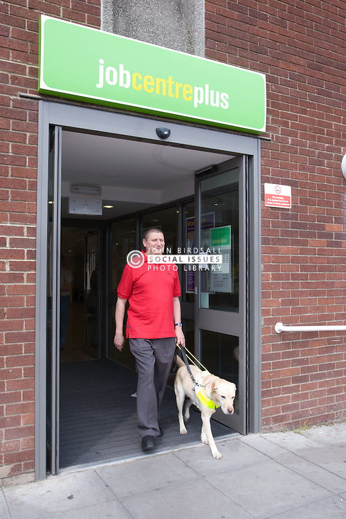 Vision impaired man and guide dog coming out of a Job Centre Plus Office,