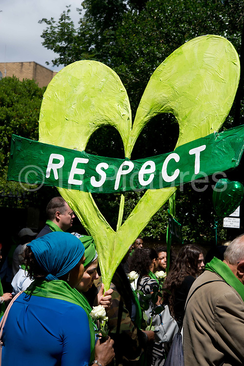 Commemoration of the first anniversary of the devastating fire of 14th/15th June  2017 in Grenfell Tower, Lancaster West Estate, West London, United Kingdom when 72 people were killed. After a 72 second silence one second for each victim survivors and family members held a silent walk to the tower. A woman holds a green heart with a green heart saying Respect.