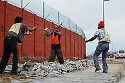 Mannen leggen stoeptegels rondom het stadion van Port Elizabeth, WK Zuid Afrika.