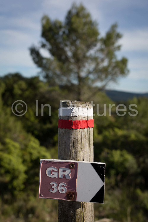 Detail of red and white stripes and signpost showing cross-country walkers the route on French national trekking network, the GR36, on 21st May 2017, in Lagrasse, Languedoc-Rousillon, south of France. Lagrasse is listed as one of Frances most beautiful villages and lies on the famous Route 20 wine route in the Basses-Corbieres region dating to the 13th century.