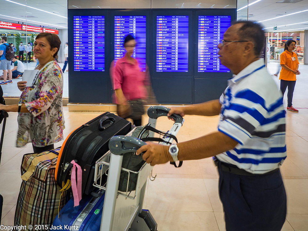 """24 DECEMBER 2015 - BANGKOK, THAILAND:  A passenger looks at the flight status board in the new domestic terminal at Don Muang (also spelled Don Mueang) International Airport. The new terminal had its """"soft"""" opening Dec. 24. Don Muang is the airport used by low cost airlines serving Bangkok and is now the largest airport in the world for low cost carriers. In 2014, more than 21million passengers used Don Muang. Don Muang International Airport is the oldest airport in Asia and one of the oldest airports in the world. It started functioning as an airfield in 1914.    PHOTO BY JACK KURTZ"""