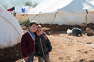 Two boys stand in front of tents at a camp for displaced persons in northern Syria. In the background an adult male is crouched beside drying laundry. Around 11,000 people were living in the camp in early 2013, driven from their homes elsewhere in Syria by violence.
