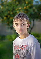 Portrait of a boy with wet hair in front of a lemon tree.