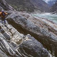 TIBET, Tsangpo Gorge, David Breashears scrambles on slick rocks in canyon under Namche Barwa, Himalays.