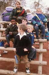 Multiracial group of boys playing on climbing frame in nursery school playground,
