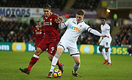 Alfie Mawson of Swansea city is challenged by Roberto Firmino of Liverpool.  Premier league match, Swansea city v Liverpool at the Liberty Stadium in Swansea, South Wales on Monday 22nd January 2018. <br /> pic by  Andrew Orchard, Andrew Orchard sports photography.