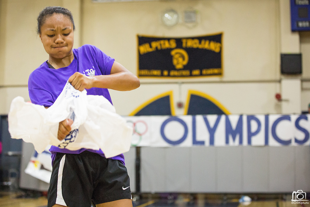 Milpitas High School senior Sarina Bolden rips apart the frozen t-shirt during the annual Trojan Olympics, where students compete in various unorthodox events for class bragging rights, at Milpitas High School in Milpitas, California, on March 27, 2015. (Stan Olszewski/SOSKIphoto)