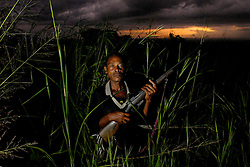 Abdilahi Musa Manga, 54, poses in the brush near Hingawali village outside Lindi, Tanzania April 28, 2006. Manga killed a female lion and also shot and injured another male lion during an outbreak of man eating. (Photo by Ami Vitale)