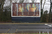 Rusting billboard showing a faded advert landscape at the Reading Services on the M4 motorway.