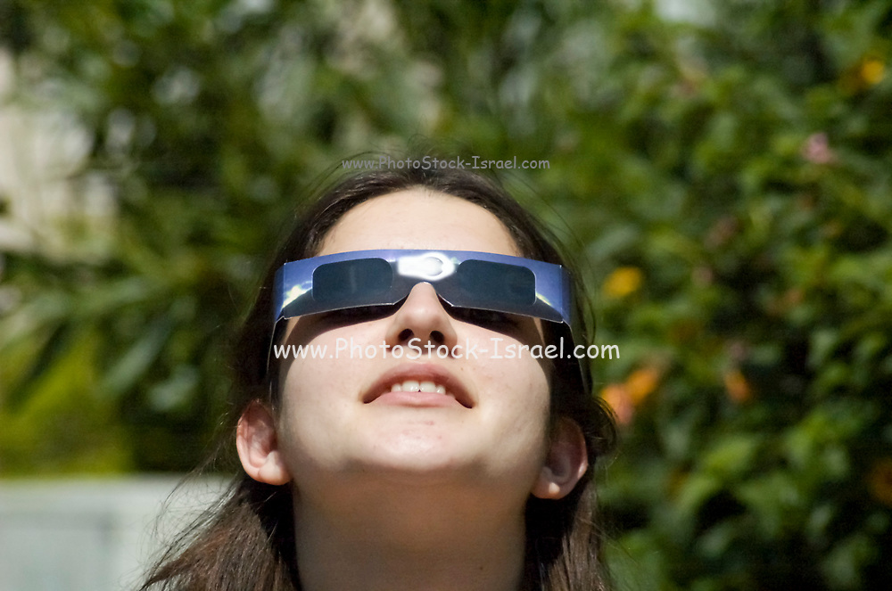 a young student, looking at the sun with special glasses, during a solar eclipse on March 29th 2006 at noon