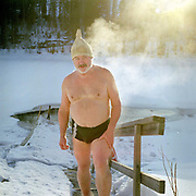 Portrait of a man wearing a woollen hat, surrounded by steam, after going ice swimming at the small lake of Vuorilampi, Jyvaskyla, Central Finland. Ice swimming takes place in a body of water with a frozen crust of ice, which requires a hole cutting in it.  In Finland, the ice swimming tradition has generally been connected with the sauna tradition and it is not seen as an ascetic or religious ritual, but as a way to cool off rapidly after staying in the sauna and as a stress relief.