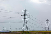 Electrical pylons running alongside wind turbines fromvthe Little Cheyne Court Wind Farm on Romney Marsh, Kent, United Kingdom. The wind farm has a nameplate capacity of 59.8 MW.