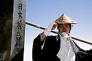 A man in traditional pilgrims's robes and hat on the summit of Mount Fuji, the highest peak in Japan. Yamanashi prefecture, Japan. August 2005