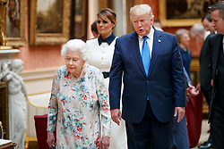 First Lady Melania Trump (centre) Queen Elizabeth II with US President Donald Trump view a special exhibition in the Picture Gallery of items from the Royal Collection of historical significance to the US, following a private lunch at Buckingham Palace in London, on day one of his three day state visit to the UK.
