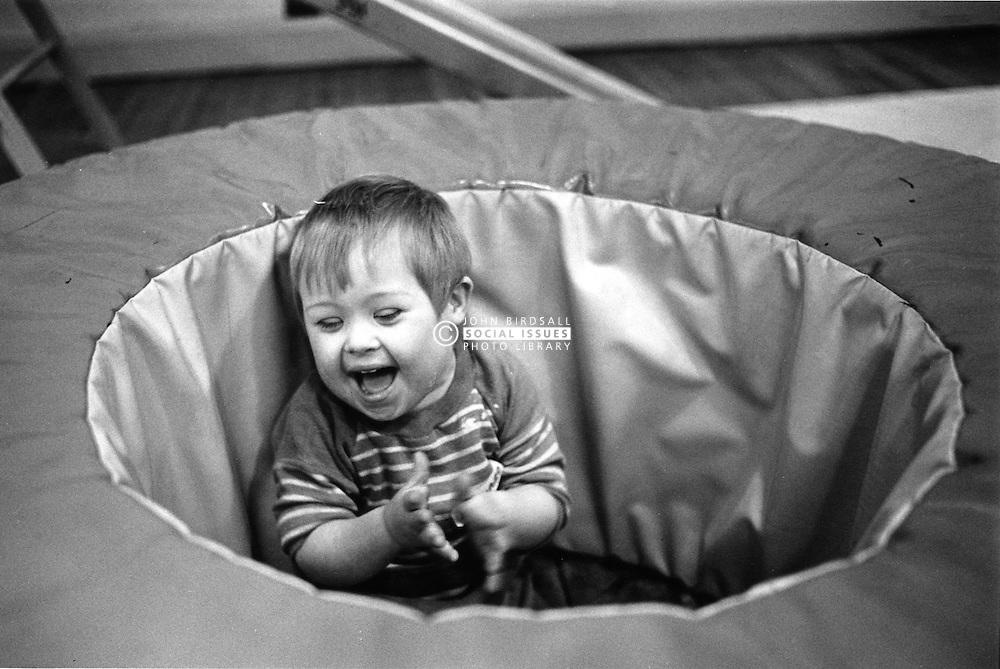 Young boy with Downs Syndrome playing in adapted play equipment,