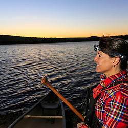 A woman prepares for a sunrise canoe paddle on Silver Lake in Piscataquis County, Maine. Near Greenville.