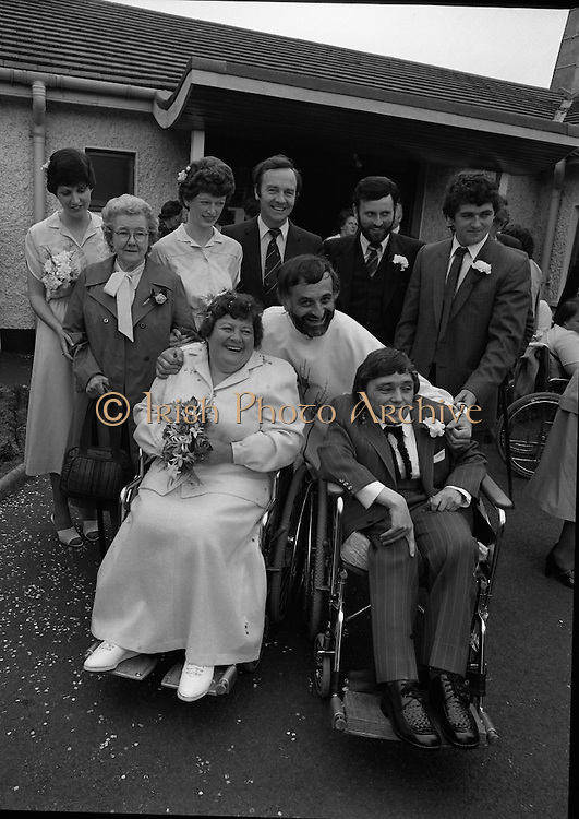 Historic Wedding Bells For Disabled Couple,  (N81)..1981..20.06.1981..06.20.1981..20th June 1981..Happy wedding bells chimed today for the first disabled couple in residential care to marry in the Republic of Ireland. The happy couple are Marie Skull and Pat Linehan and they were married in a special ceremony in The Cara Cheshire Home in the Phoenix Park. Both Marie and Pat are confined to wheelchairs because of their disabilities. After honeymoon, they will make their home in specially adapted quarters within the Cheshire residence. The New Mr and Mrs Linehan pose for wedding pictures outside the Cheshire home. They are accompanied by family and friends and by the Minister for Health, Dr Michael Woods TD..If you know the names of the priest and family members why not let us know and we will add them to the caption.
