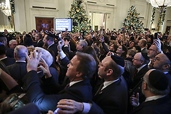 guests take pictures as they attend a Hanukkah reception with President Donald Trump in the East Room of the White House on December 6, 2018 in Washington, DC. (Photo by Oliver Contreras/SIPA USA)