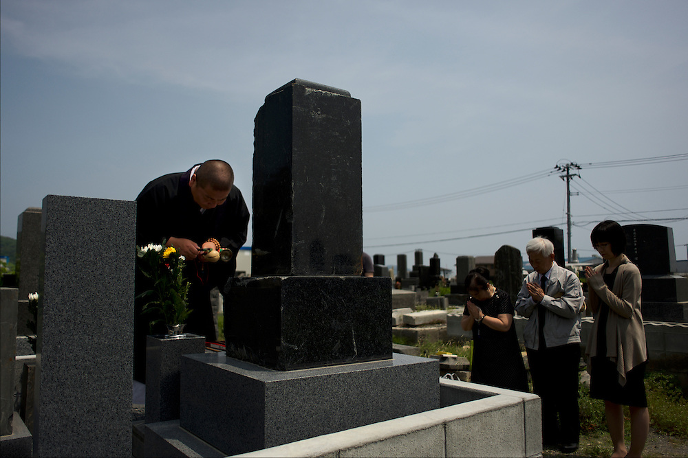 A family attend a religious ceremony, at local cemetery in Ishinomaki, in memory of a relative who lost his life during the  devastating tsunami that hit the east coast of Japan in 2011.