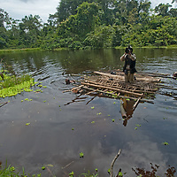 Indian guides help steer a photographer on a raft on a remote lake in Peru's Amazon Jungle. Also in the water are Pirana, Caiman, snakes & other hazards.