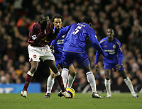 Photo: Lee Earle.<br /> Arsenal v Chelsea. The Barclays Premiership. 18/12/2005.Arsenal's Lauren (L) winces in pain after clashing with Mickael Essien.