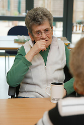 Wheelchair user in conversation at a resource for people with physical and sensory impairment.