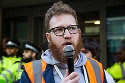 London, UK. 26th February, 2019. Daniel, a representative of the National Union of Rail, Maritime and Transport Workers (RMT), addresses mainly migrant striking outsourced workers belonging to the Independent Workers of Great Britain (IWGB), United Voices of the World (UVW) and Public and Commercial Services Union (PCS) trade unions working at the University of London (IWGB), Ministry of Justice (UVW) and Department for Business Energy and Industrial Strategy (PCS), together with representatives of the National Union of Rail, Maritime and Transport Workers (RMT) Regional Council, taking part in a 'Clean Up Outsourcing' demonstration to call for an end to the practice of outsourcing. The demonstration was organised to coincide with a significant High Court hearing of an application by the IWGB for judicial review of a decision by the Central Arbitration Committee (CAC) not to hear their application for trade union recognition for the purposes of collective bargaining with the University of London.