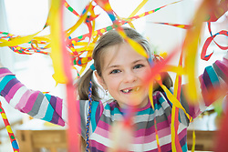 Portrait of girl with blowout paper streamer at birthday party, smiling