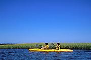 Two women in tandem kayak navigating through marsh grass along Cape Cod National Seashore, Eastham, Cape Cod