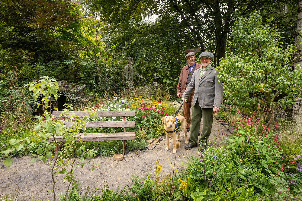 Garden designers Jonathan Smith and Adam Woolcott  in the Artisan Garden at RHS Chelsea which they created this year in celebration of 90 years of guide dog partnerships in Britain. They are pictured with guide dog puppy in training, Flash. Flash is a female, eight-month-old Labrador named for Guide Dogs's 90th anniversary. <br /> Picture date: Monday September 20, 2021.<br /> Photograph by Christopher Ison ©<br /> 07544044177<br /> chris@christopherison.com<br /> www.christopherison.com