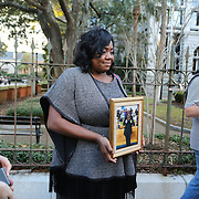 Charleston, SC - January 11, 2017: Rose Simmons, daughter of Rev. Daniel Simmons, holds up a photo of her father, Rev. Daniel Simmons, before she speaks to the media outside of US District Court on Broad Street in downtown Charleston just after the formal sentencing of Dylann Roof for the killing of 9 people at Emanuel AME Church in June of 2015. (CREDIT: LOGAN R. CYRUS FOR THE NEW YORK TIMES)