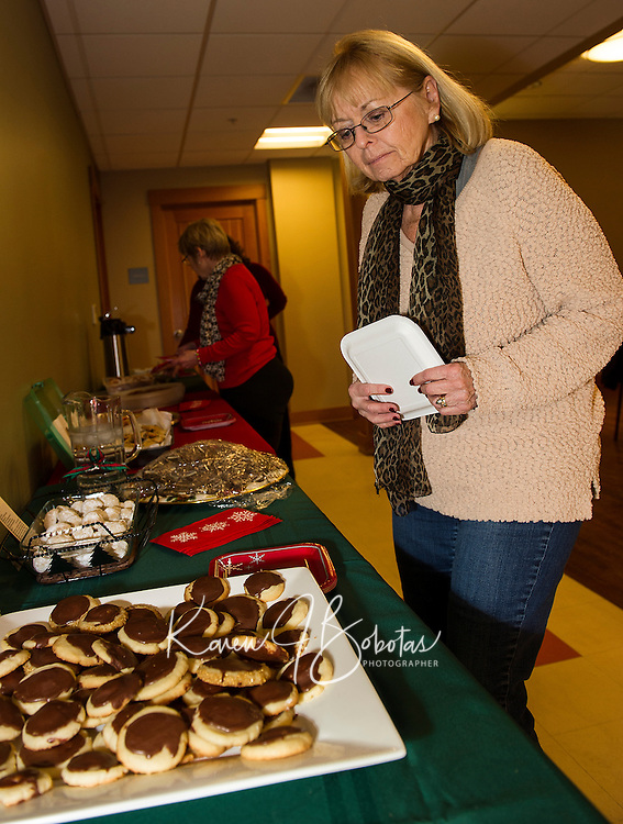 Beverly Shanley chooses from salted caramel pretzel chocolate chip cookies, butterballs, sugar cookies, angel wings, ginger snaps, peanut butter and chocolate toffee brittle and brown eyed susan cookies shared during the Cookie Swap at the Gilford Library on Tuesday evening.  (Karen Bobotas/for the Laconia Daily Sun)