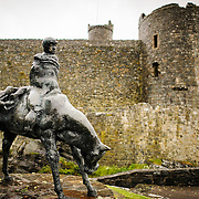 The Two Kings statue at Harlech Castle in northwestern Wales. Sculpted by Ivor Roberts-Jones and unveiled in 1984, the sculpture depicts the Mabinogion story of Branwen, a lament of the folly and carnage of war. In the sculpture, the figure of Bendigeidfran, bearing the body of his nephew Gwern, symbolises the sorrowful burden that love can be. Harlech Castle in Harlech, Gwynedd, on the northwest coast of Wales next to the Irish Sea, was built by Edward I in the closing decades of the 13th century as one of several castles designed to consolidate his conquest of Wales.