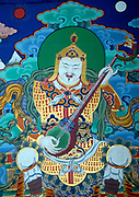 Mural painting of Dhritarastra.   According to buddhist teachings the Four Heavenly Kings, Four Great Kings, Four Guardian Kings watch over the four directions. Paintings of all four are often seen in temple and monastery entrances. Dhritarastra  watches over the East. He is white. His symbols are a pipa, a stringed lute-like musical instrument. He is attended by Gandharvas, nature spirits with great musical ability.   The style It originates in Chinese and Tibetan buddhist art. Paro Dzong, Druk Yul,  Bhutan. 10 November 2007