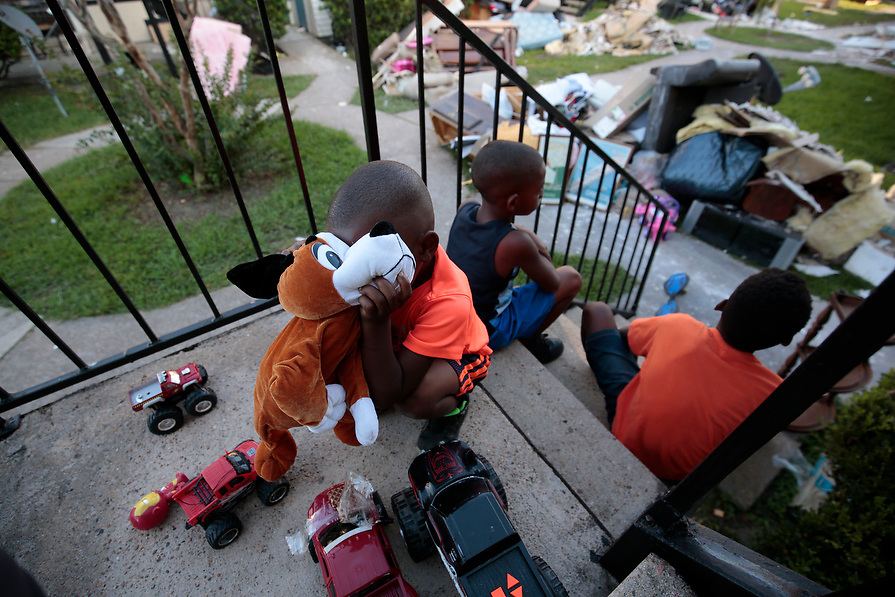 From left, Kameron Smith, 4, Darius Smith, 9, and Deandre Green, 10, play with toys that they found in the piles of destroyed property at Crofton Place Apartments in the aftermath of Hurricane Harvey in Houston, Texas, U.S. September 8, 2017. The children's apartment was destroyed by the flood waters.
