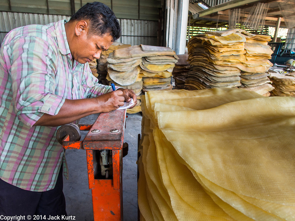 """15 DECEMBER 2014 - CHUM SAENG, RAYONG, THAILAND: A worker weighs rubber sheets bought from farmers at a business that buys rubber and resells it to processing plants in Chum Saeng, Thailand. Thailand is the second leading rubber exporter in the world. In the last two years, the price paid to rubber farmers has plunged from approximately 190 Baht per kilo (about $6.10 US) to 45 Baht per kilo (about $1.20 US). It costs about 65 Baht per kilo to produce rubber ($2.05 US). Prices have plunged 5 percent since September, when rubber was about 52Baht per kilo. Some rubber farmers have taken jobs in the construction trade or in Bangkok to provide for their families during the slump. The Thai government recently announced a """"Rubber Fund"""" to assist small farm owners but said prices won't rebound until production is cut and world demand for rubber picks up.     PHOTO BY JACK KURTZ"""