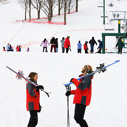 A man and woman head to the slopes at the Quechee Ski Hill in Quechee, Vermont.