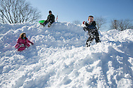 Needham, MA 02/10/2013<br /> Connor Falahee, age 7, throws a snow ball at his father from atop a giant pile of snow in the Needham High School parking lot on Sunday afternoon.
