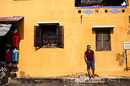 A young vietnamese man leans against a colorful wall in a street of Hoi An, Vietnam, Southeast Asia