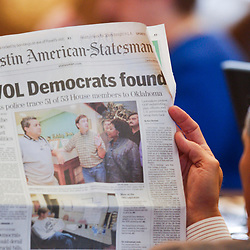 Images from 2003's Democratic walkout in the Texas House from May 12-13, 2003 during the 78th session of the Texas Legislature include a state representative reading the local paper on the House floor.