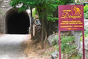 Sign pointing to the winery Vinarija Dingac with a sign of donkey. Pointing to the road tunnel. Potomje village, Dingac wine region, Peljesac peninsula. Dingac village and region. Peljesac peninsula. Dalmatian Coast, Croatia, Europe.