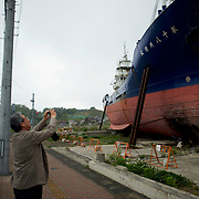 A tourist takes photographs of a large vessel grounded amid a flattened residential neighbourhood in Kesennuma. The vessel was washed from the port during the 2011 tsunami that struck over the coastal areas of Japan.