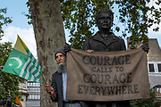 A man stands next to Gillian Wearings 'Courage calls to courage everywhere' sculpture as pro Kashmir campaigners gather at Parliament Square on the 3rd September 2019 in London in the United Kingdom. Protesters gather near the statue of Mahatma Gandhi in solidarity following Indian Prime Minister Narendra Modi's Independence Day speech removing special rights of Kashmir as an autonomous region.