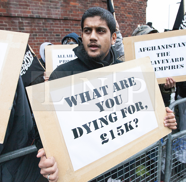 """© Licensed to London News Pictures . London , UK . Siddhartha Dhar (C holding a sign that reads """" What are you dying for , £15k ? """") at a Muslims Against Crusades demonstration on Exhibition Road in London on the anniversary of Armistice Day in London , on November 11, 2010. There has been speculation that Siddhartha Dhar is this the new 'Jihadi John', who appeared in a recent ISIS video. . Photo credit : Joel Goodman/LNP"""