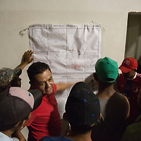 some of the thousands on the migrant caravan look at a map of Mexico on the wall of a refuge in Juchitán, Oaxaca