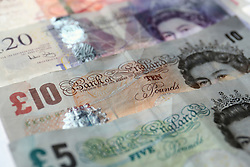 File photo dated 07/11/14 of Fifty, Twenty, Ten, and Five pound notes. A debt charity has warned that thousands of clients are being hit with unarranged overdraft penalty charges averaging £225 a year.