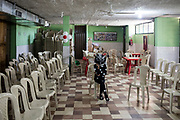 A young girl dressed as a mosquito sits in an empty classroom after participating in a presentation about the dangers of mosquito borne disease.