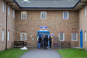 A group of prisoners are escorted through the prison grounds to the residential wings by a prison officer. HMP Send, closed female prison. Ripley, Surrey.